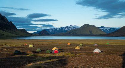 Shluk ultralehkých turistických stanů postavených v přírodě obklopené horami
